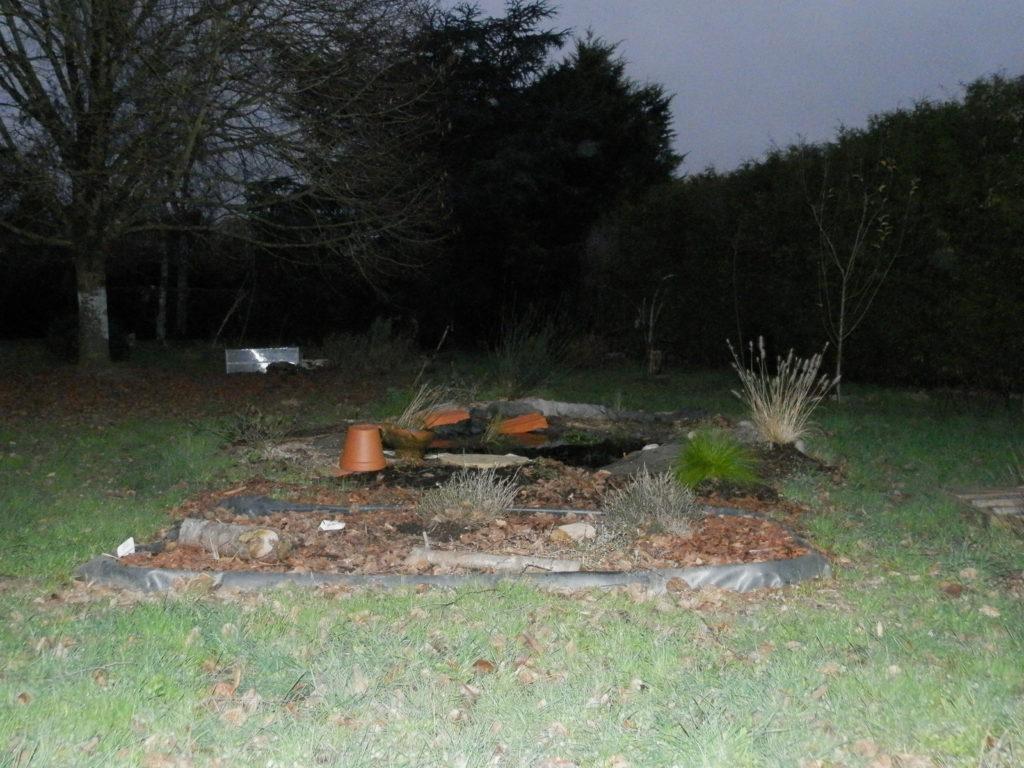 Coin du jardin avec au premier plan une mini-tourbière artificielle, puis une mare à filtration naturelle, des fruitiers sur le côté (pommiers, groseilliers) et des arbres de haut jet au fond (tilleul, cèdre)